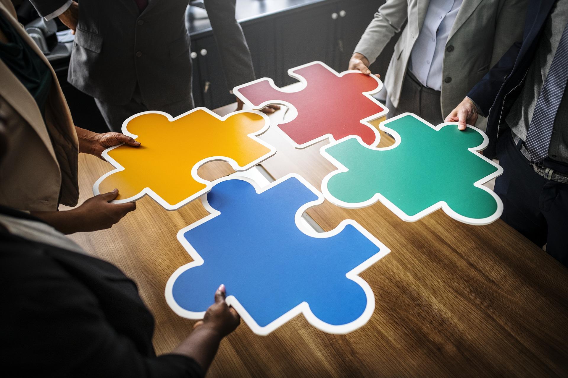 Quatre personnes tiennent chacune la pièce d'un puzzle et les assemblent sur une table.