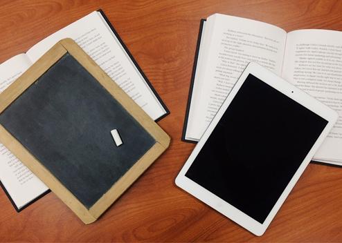 L'image représente 2 livres. Sur le livre de gauche est posée une ardoise, sur celui de droite une tablette numérique.