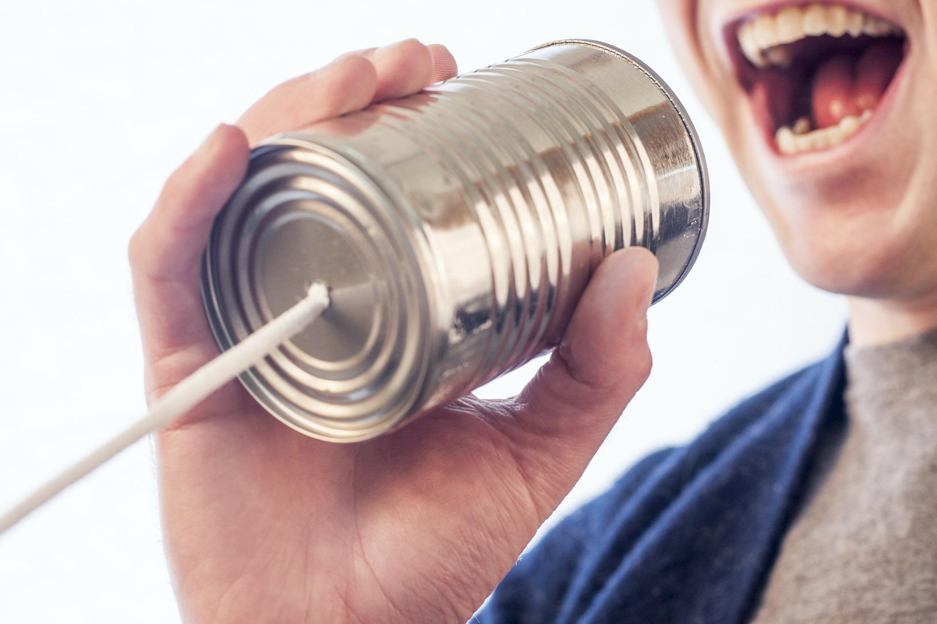 Personne qui parle dans un téléphone fabriqué à partir d'une canette de conserve reliée à un fil.